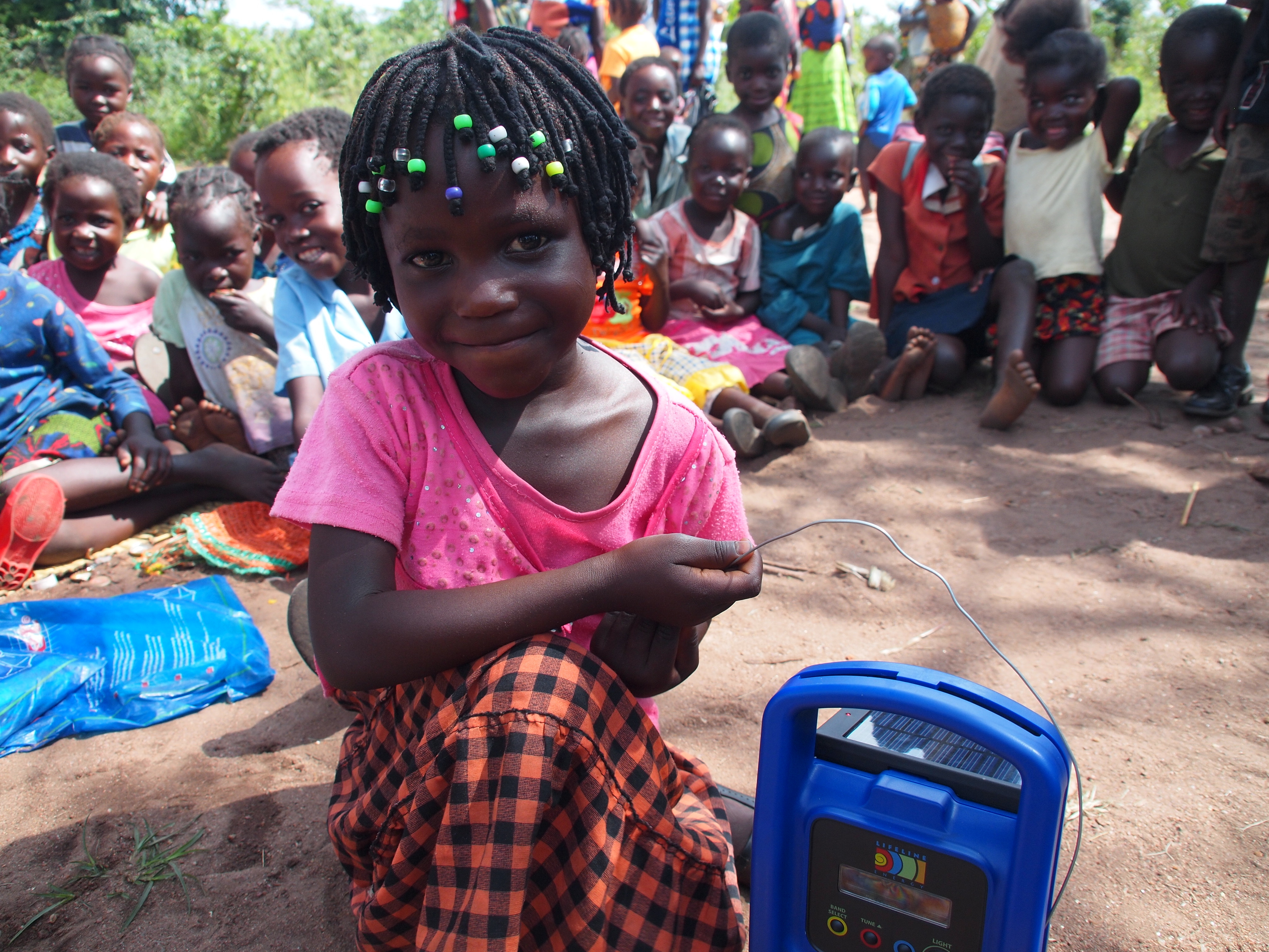 Felicia, an early Taonga Market student, holds one our solar and wind-up radios. The Learning at Taonga Market programme reaches children in rural areas, 35% of which are orphaned.