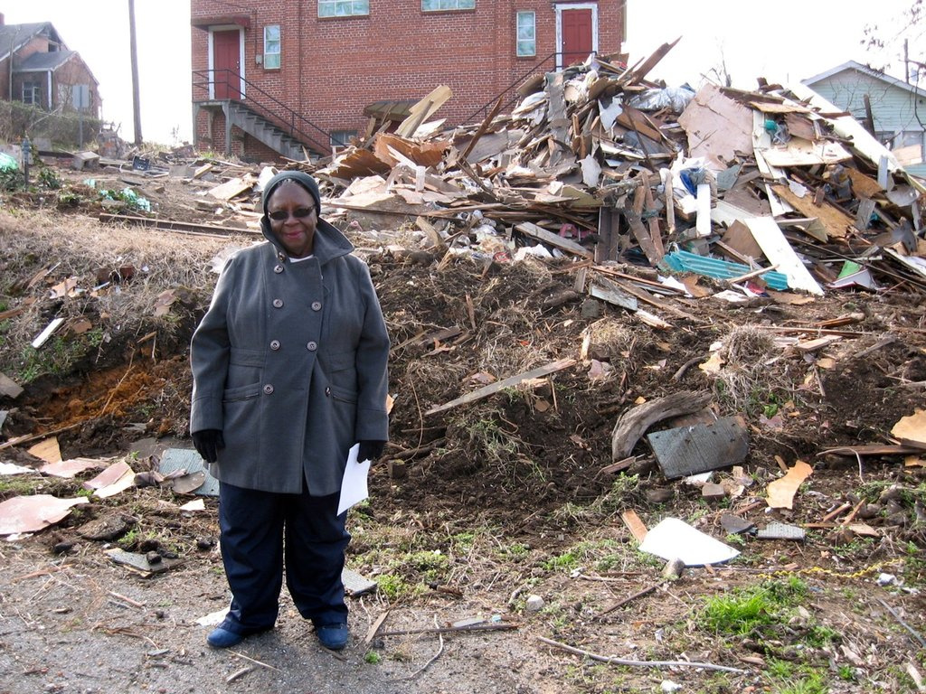 Ms. Patterson in front of her demolished home.