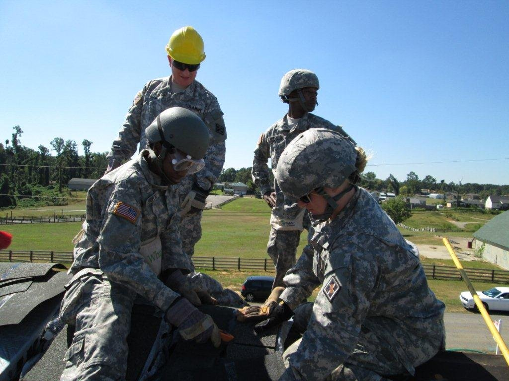 Soldiers install shingles on the Smith home