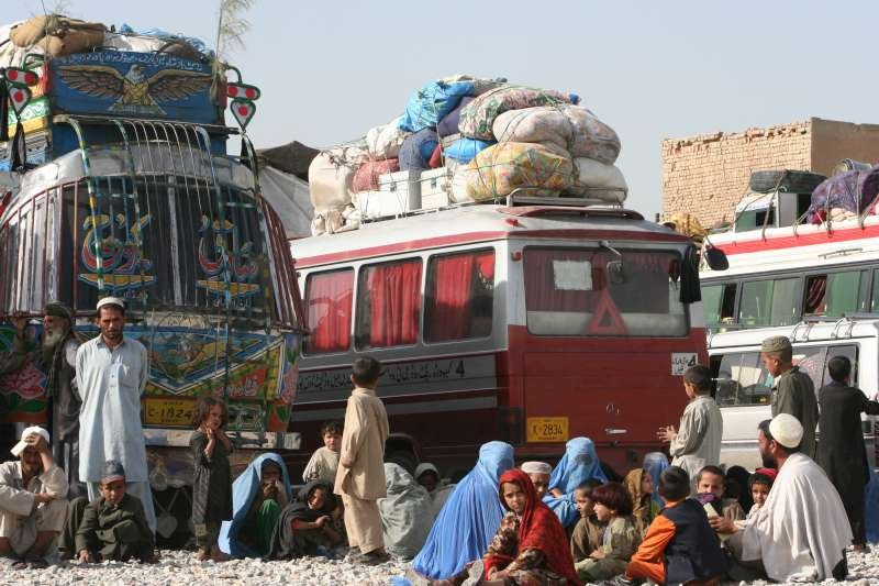 Afghan refugees wait to return home by bus.