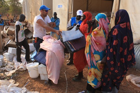 UNHCR distributes blankets to refugee women.