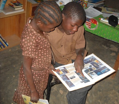 Young Girl Reading Aya with Her Brother