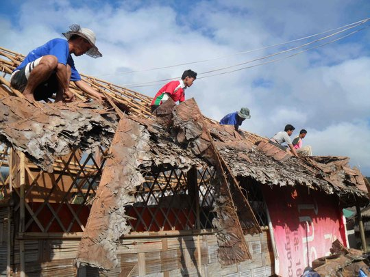 Residents building the new roof we helped provide