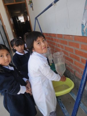 Girl using the hand washing station at a school