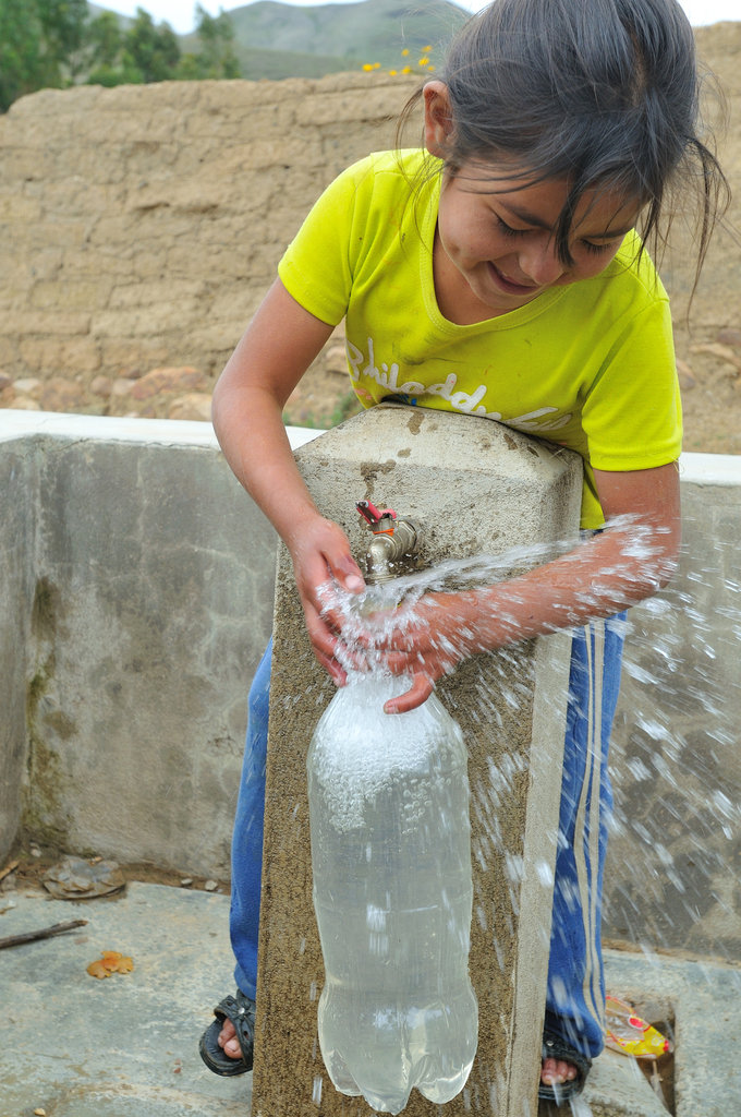 A girl fills a plastic bottle with tap water. Solar Water Disinfection is a simple method to disinfect drinking water: Water is filled in common soft drink bottles and exposed to sunlight for at least six hours, making it thus safe for consumption.