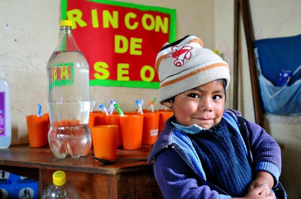 """Valent?n Choquehanca is posing in front of the newly established """"""""healthy corner"""""""" at his school. At the healthy corner, safe drinking water is stored, alongside with items of personal hygiene. Water disinfection and hand washing are two simple solutions to improve health of children like Valent?n."""