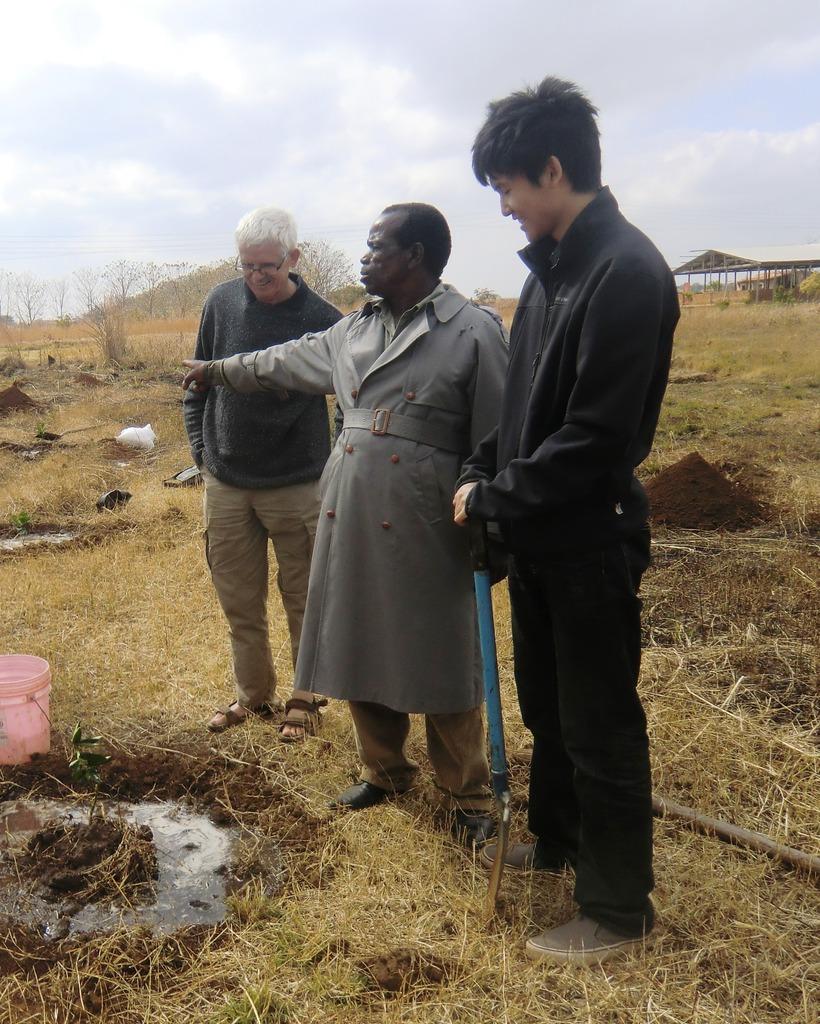 Chris, Moses and Kai planting a tree