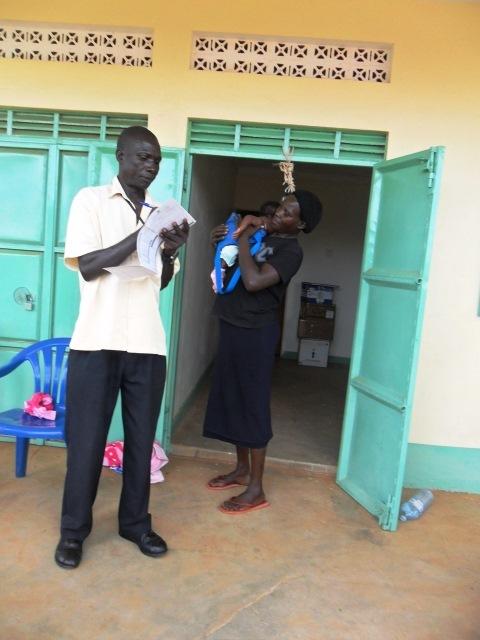Robert weighing the baby before immunisation