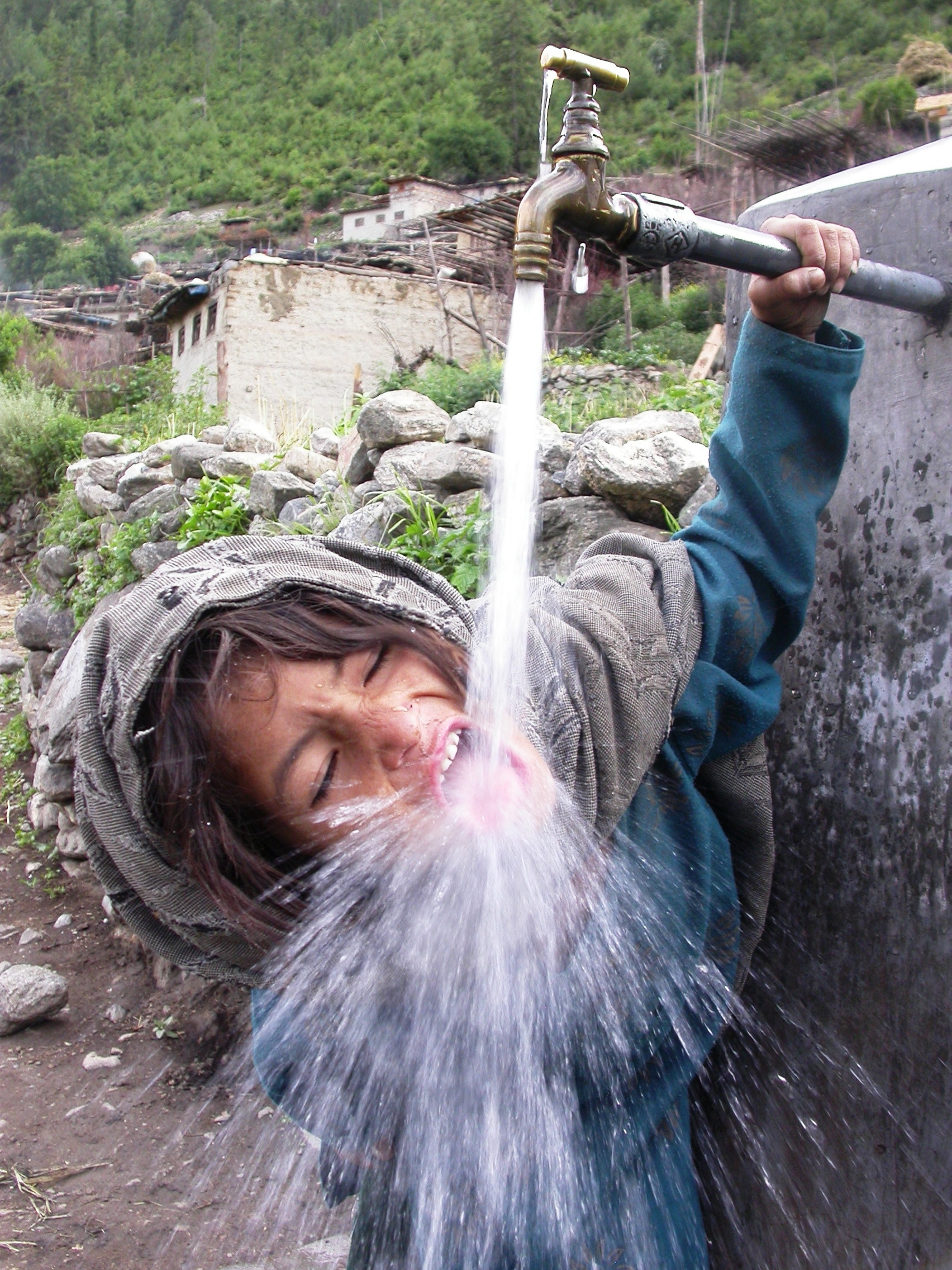 "Young Nepalese enjoying potable water in her remote village of Mohorigaun . This water has been set up thanks to the work of RIDS-Nepal and its project """"Family plus 4"""". In those villages in the Himalayan mountains, before the project, villagers do not have access to potable and running water."