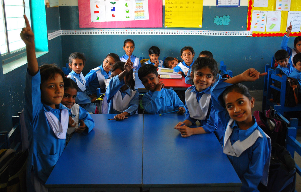 Students in DIL Chatro School (a primary school) raise their hands during a school lesson. The safe, clean classroom furnished with appropriate supplies is just one of the ways that DIL supports its students.