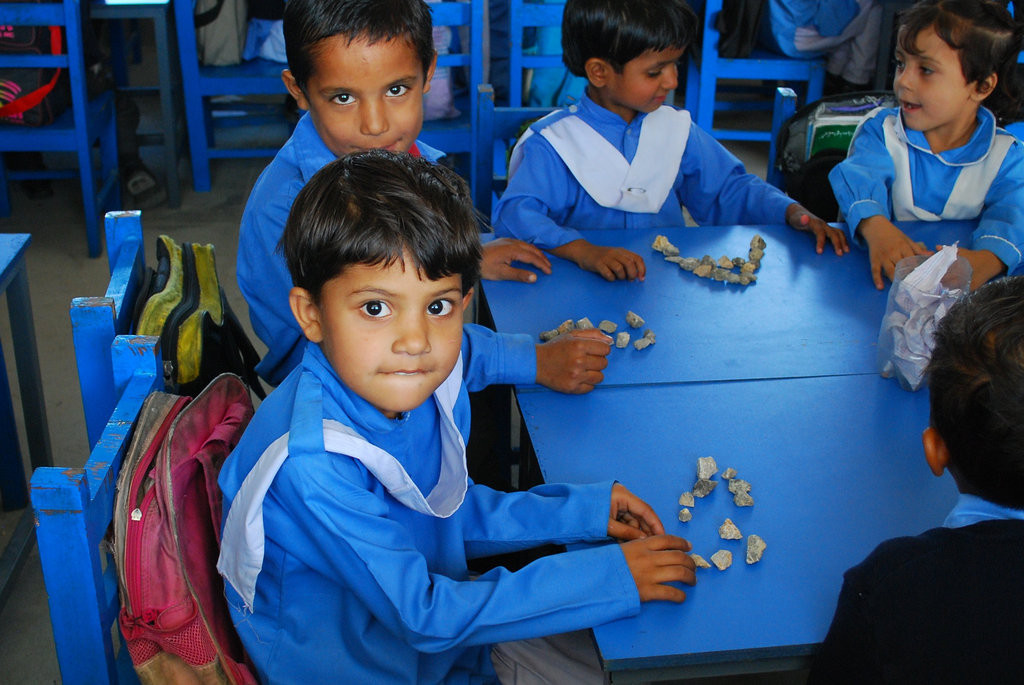 A young male student in DIL Chatro School looks at the camera while doing a hands-on activity lesson involving rocks. Our teachers are trained on innovative and interactive learning activities for their students.