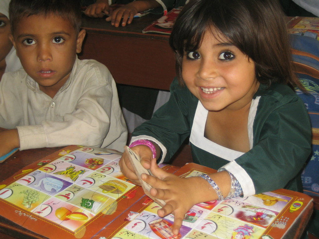 A young female DIL student shows off a wooden card she holds while doing an activity. Female students make up nearly 70% of the DIL student population, an impressive percentage as the national literacy rate for women can be as low as 8% in rural areas.